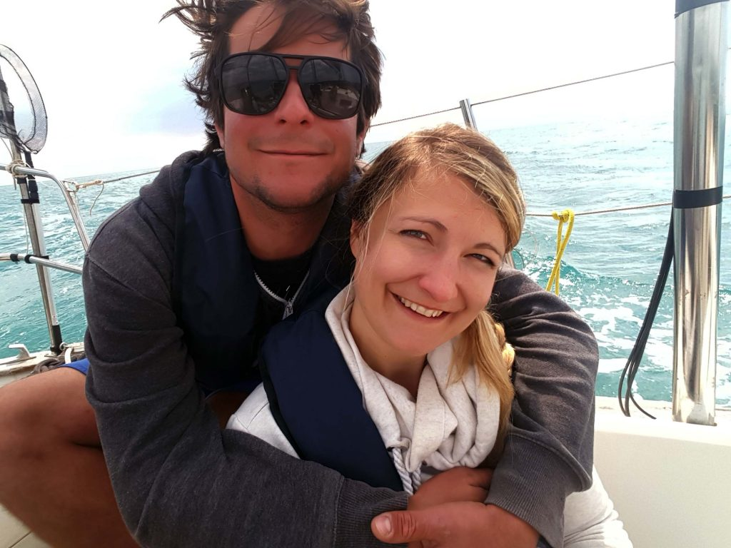 a couple hugging on a sailboat
