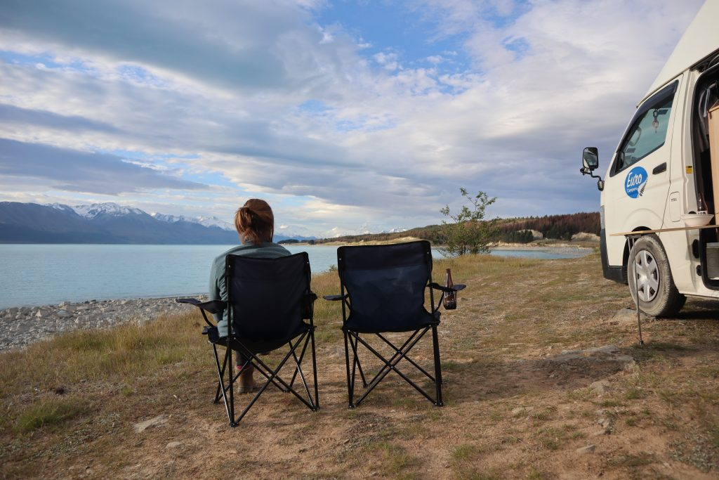 a girl looking out over views of new zealand with her one year old asleep in a campervan