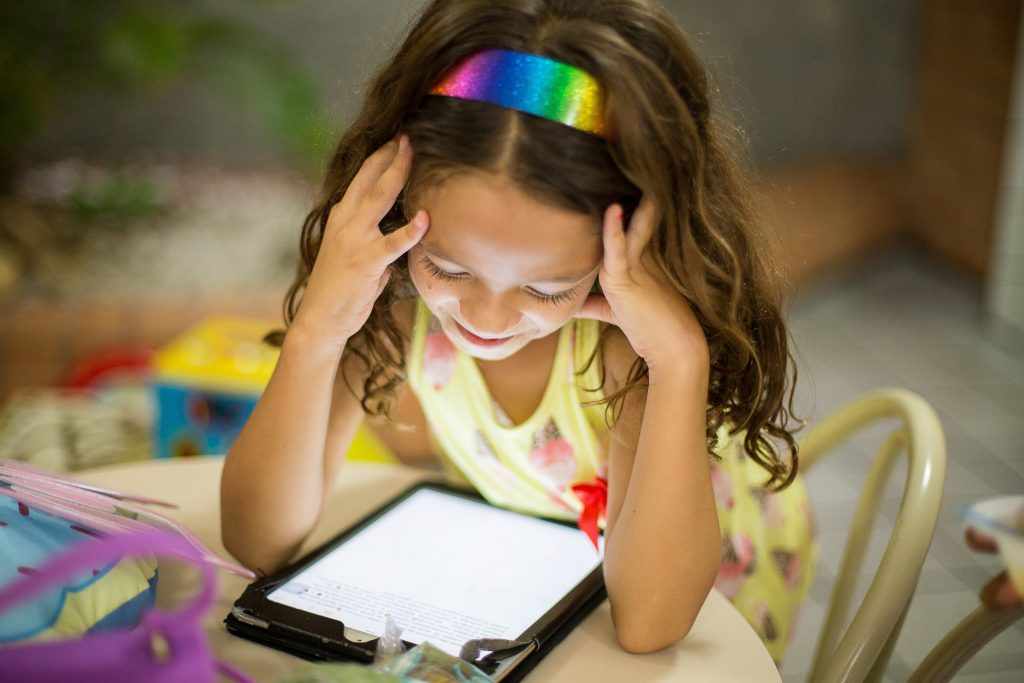 a girl looking at a tablet full of educational websites for homeschooling