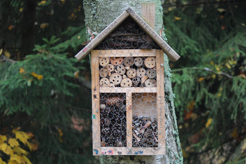 a bug hotel on a tree in a kids garden