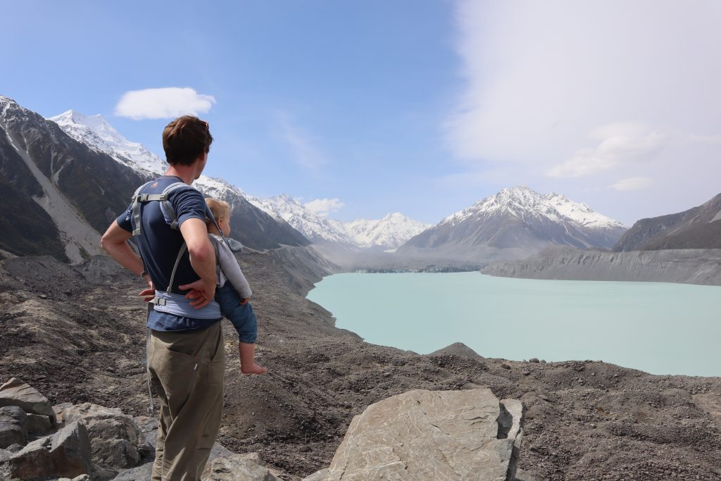 a man and baby in new zealand looking out at a lake view