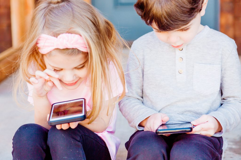 two children sat on a step looking at educational websites on their phones