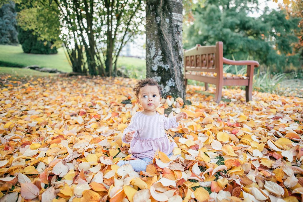a child sat outdoors in a pile of leaves