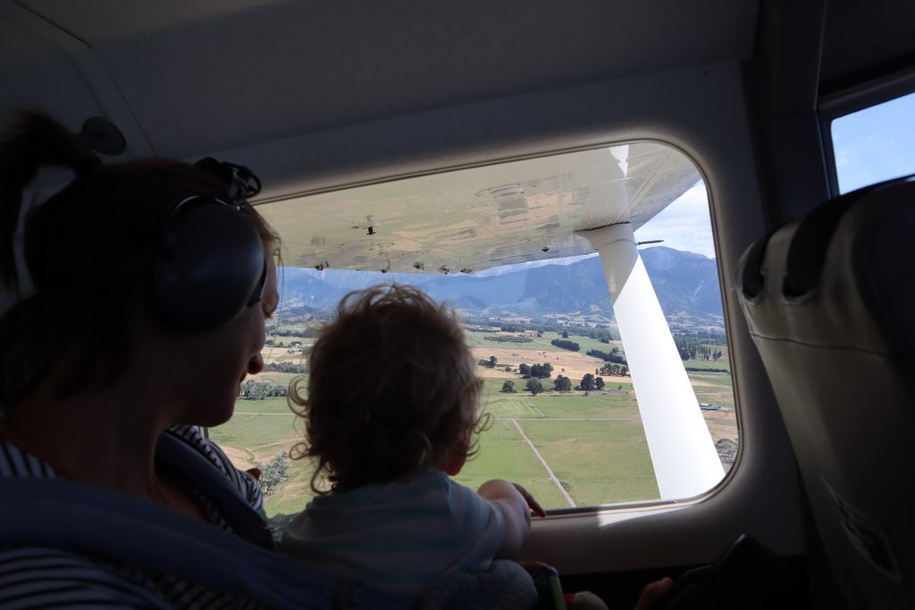 a toddler checking out the views of new zealand from a plane