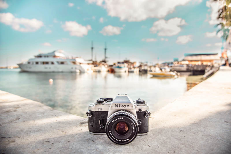 a nikon camera sat on a harbour wall ready to be used for a blogging photo shoot