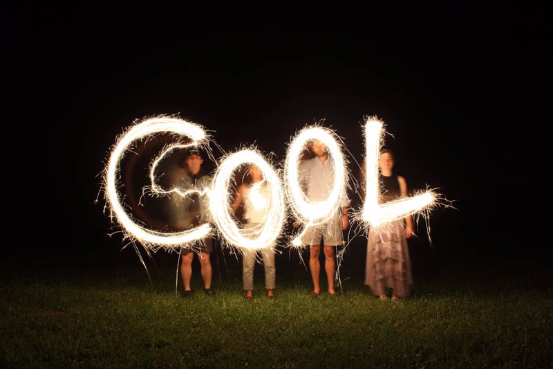the word 'cool' written by sparklers at night