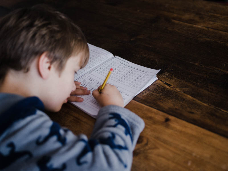 a boy writing down his spellings in a note book