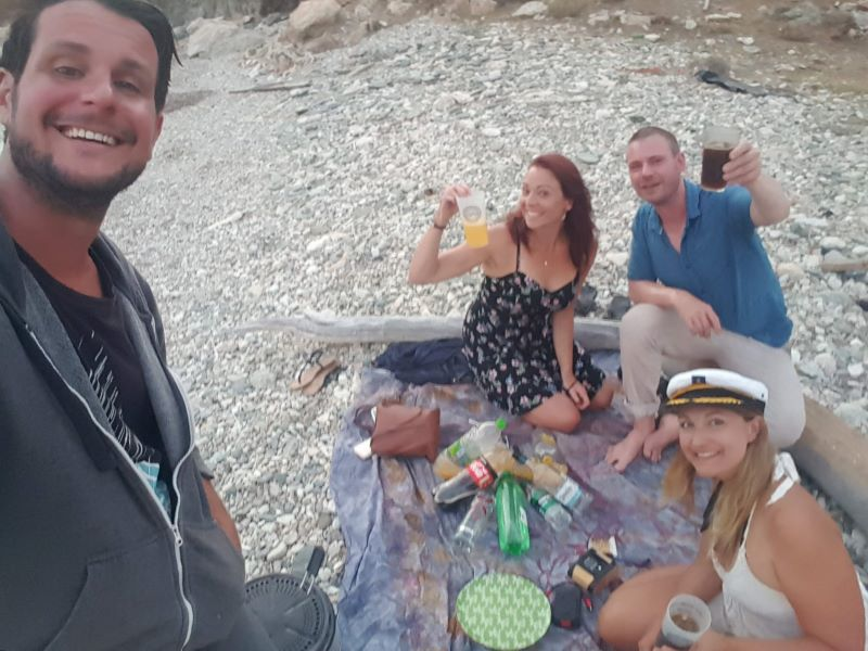 four people enjoying drinks on a beach after crewing on a sailboat