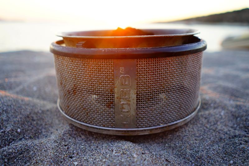 a cobb bbq on the beach with the sun setting behind