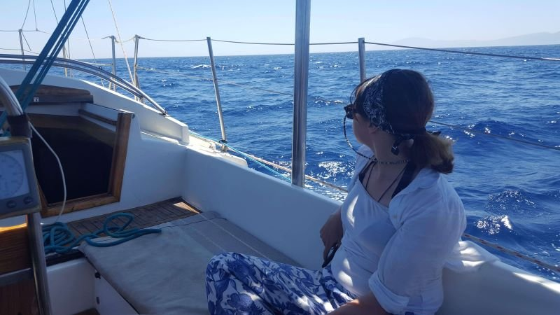 A crew member relaxing at sea in the cockpit of a sailboat