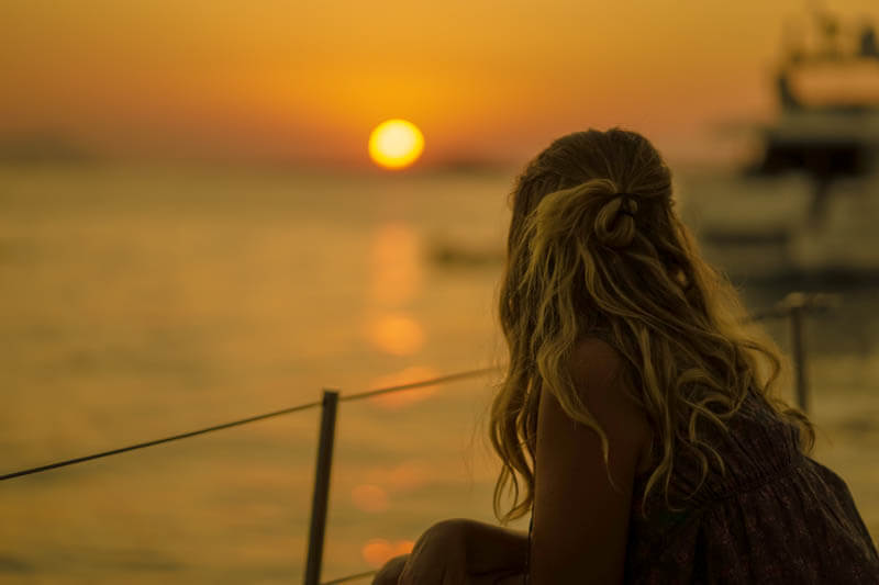 a girl looking out to sunset from a sailboat