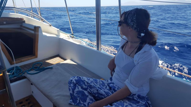 a girl on a sailboat watching the waves go by