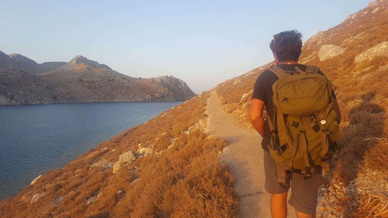 a man walking along one of the top 10 hiking trails in Symi