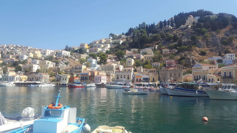 symi town looking at the bright, colourful houses from across the harbour