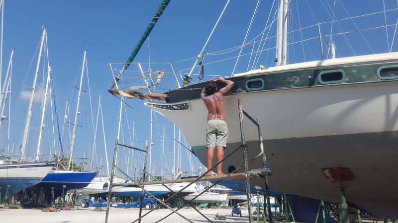 A man doing work on his sailboat to keep the cost of sailboat ownership down