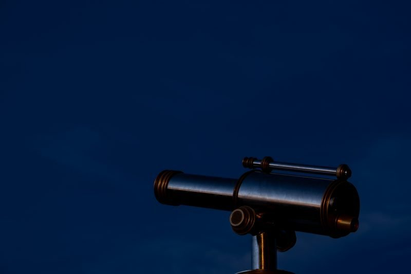 a telescope in front of a night sky in england in the winter