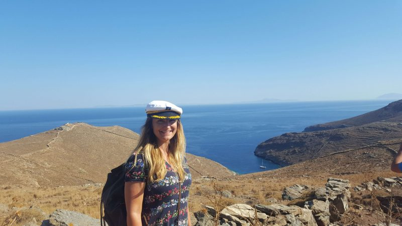a girl in a sailors hat standing on the top of a mountain