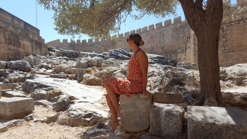 a girl sat among ancient ruins