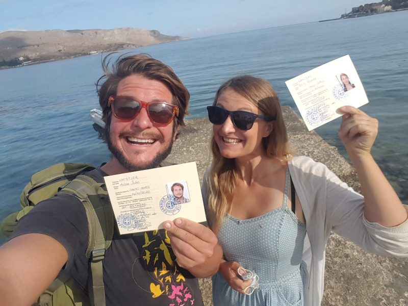a couple holding up their greek residency cards