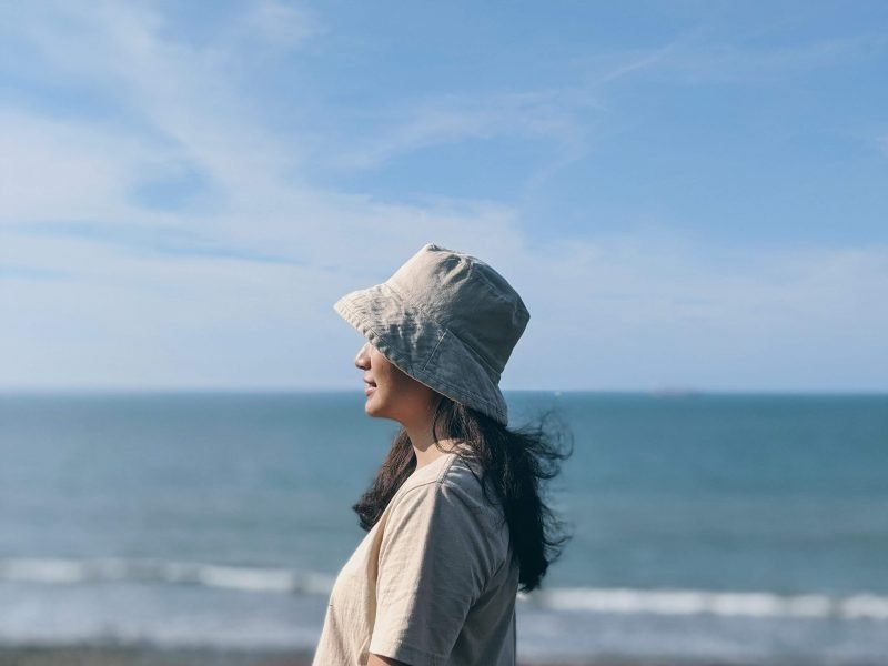 a girl looking out to sea in the best hat for sailing