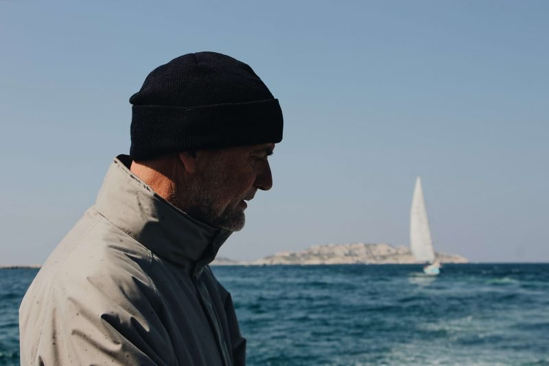 a man in a hat for sailing looking out at a sailboat on the water