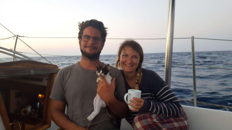 a couple and their cat on a sailboat at sea