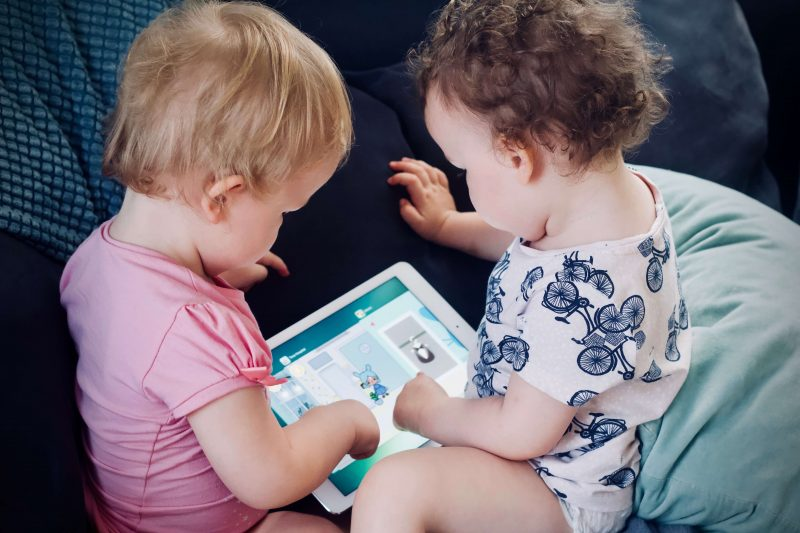 two babies reading on a tablet