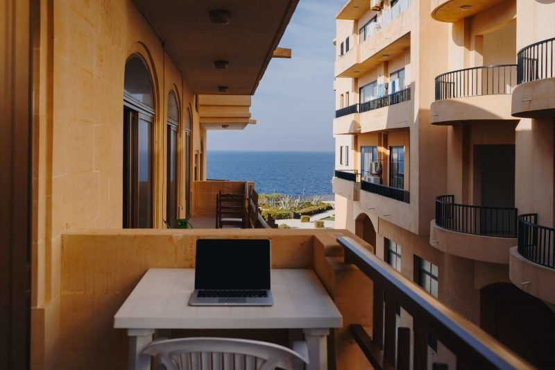 a digital nomad working on a spanish balcony overlooking the sea