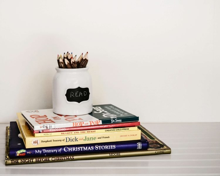 some books in a pile on a childs desk