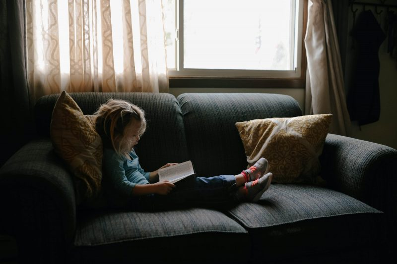 a reluctant reader reading on a sofa on their own