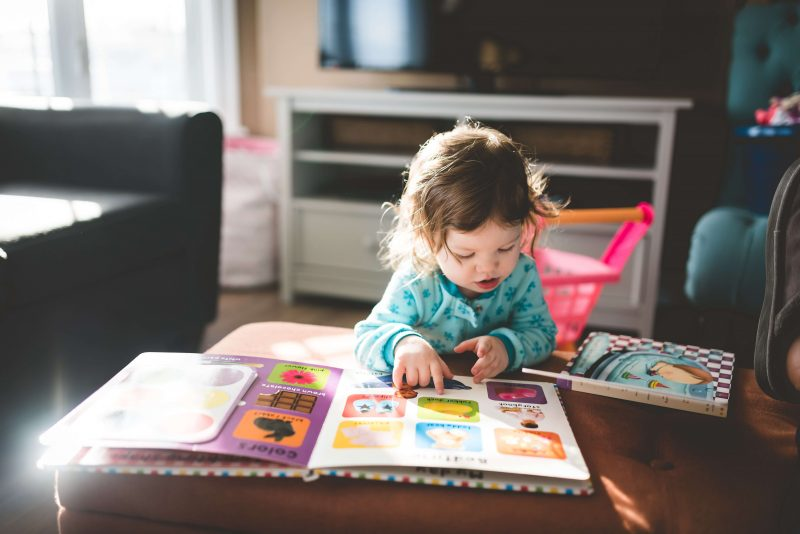 a baby reading a book at a table