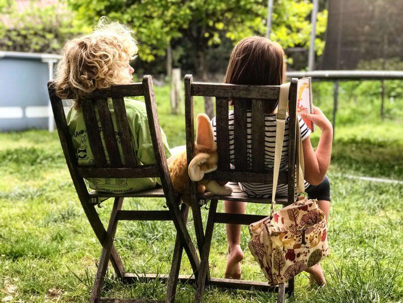 two children reading in deckchairs
