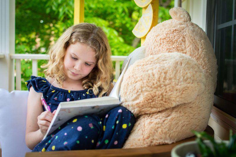 a reluctant reader child reading to her teddy bear