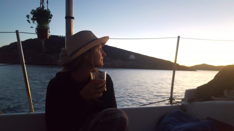 a girl wearing her best sailing hat while drinking wine on a sailboat