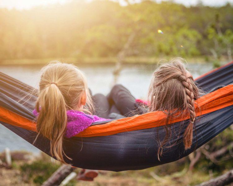 two girls reading in a hammock