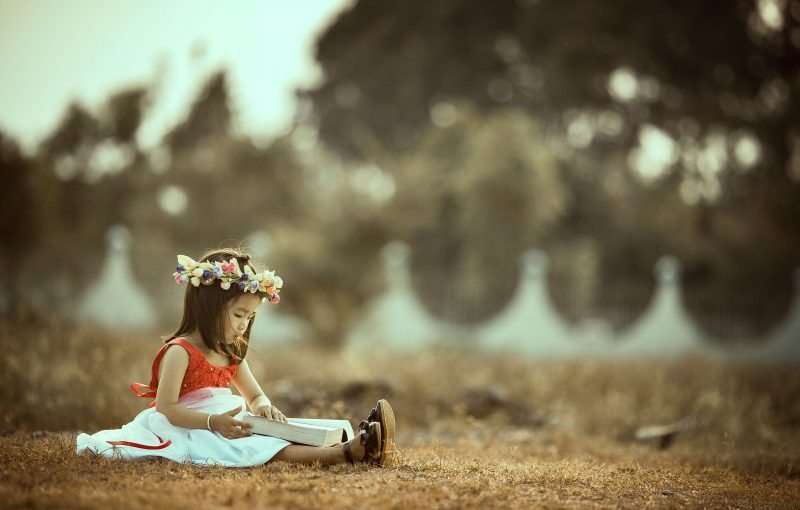 a little girl reading a book on the grass