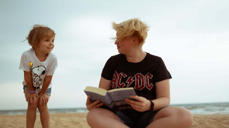 a woman reading to a reluctant reader on the beach