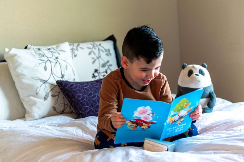 a little boy reading on a bed