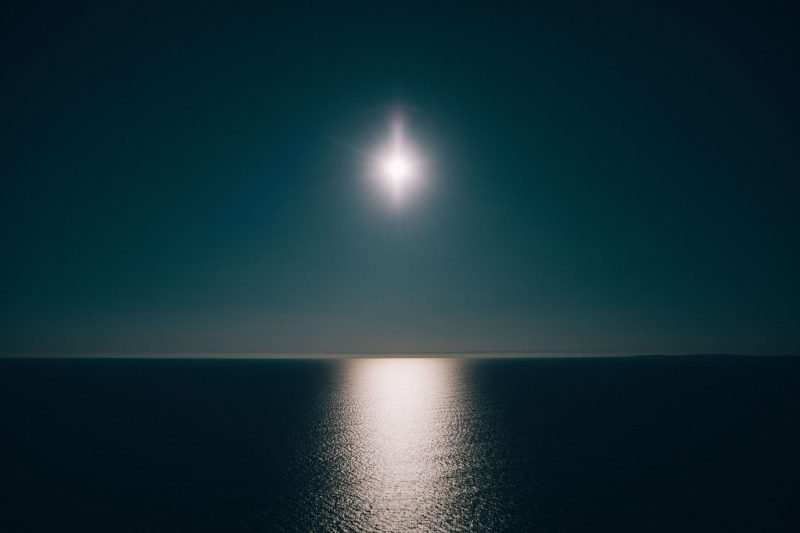 the moon reflecting on the sea during a night sail, lit only by the best sailing headlamp