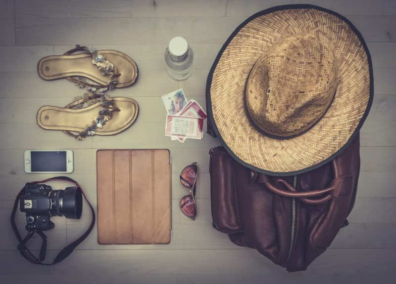 gift items to pack for a digital nomad like a hat, some sandals and a camera