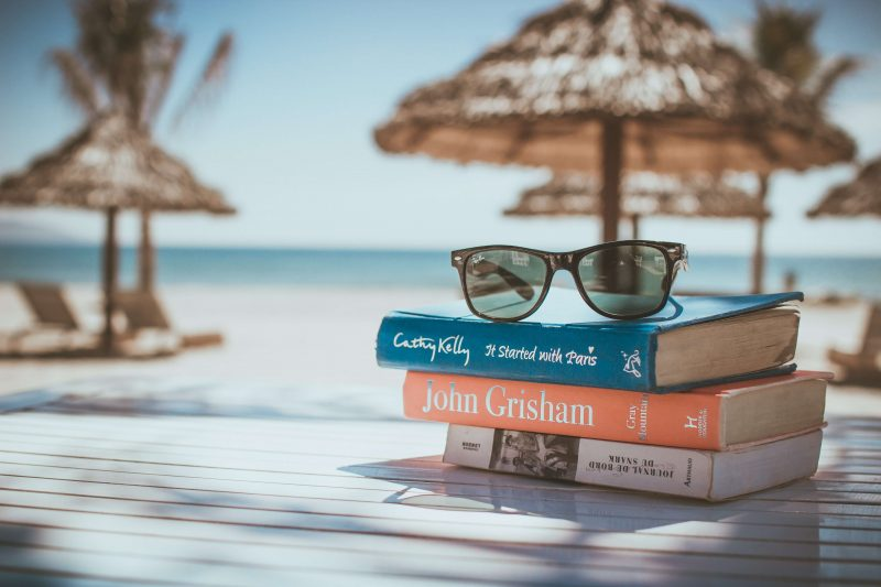 the best travel stocking stuffer books on a table by a pool