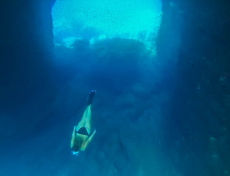 a girl diving in greece's clear waters