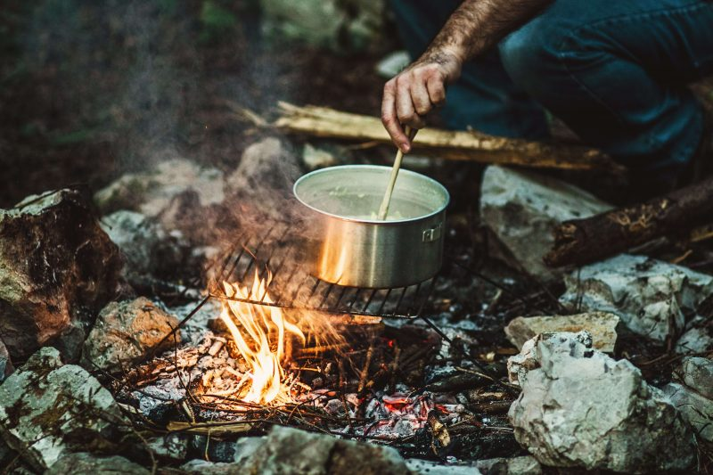 some cooking outdoors on a campfire in the winter