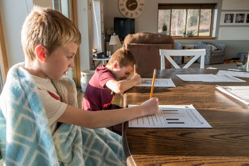 children at homeschool doing worksheets on a table