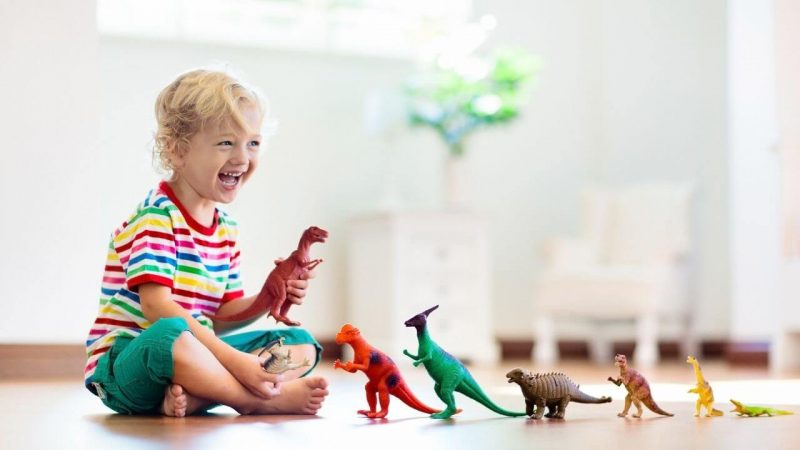 a boy playing with toy dinosaurs