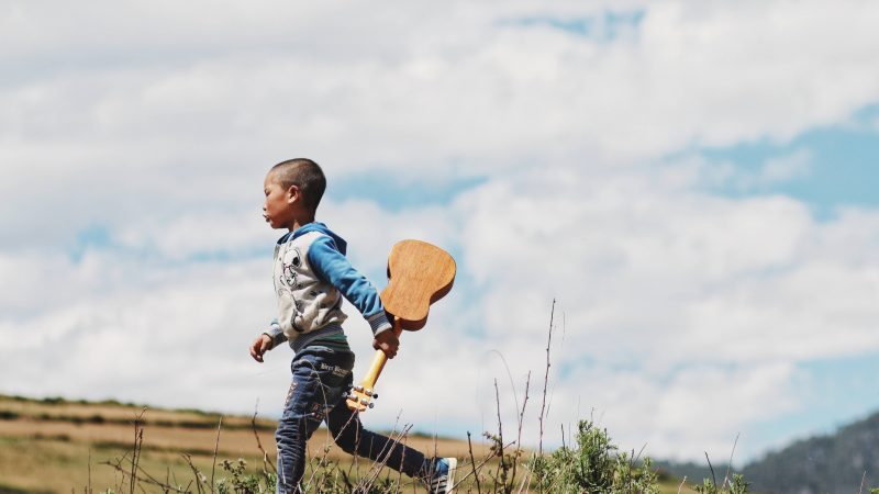 a boy carrying a guitar to homeschool lessons
