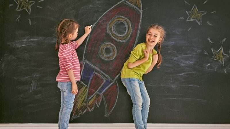 two kids drawing a rocket on a chalkboard for imaginative hook ideas for space