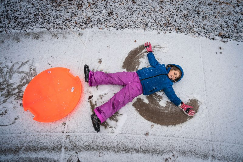 a kid enjoying making snow angels in the winter