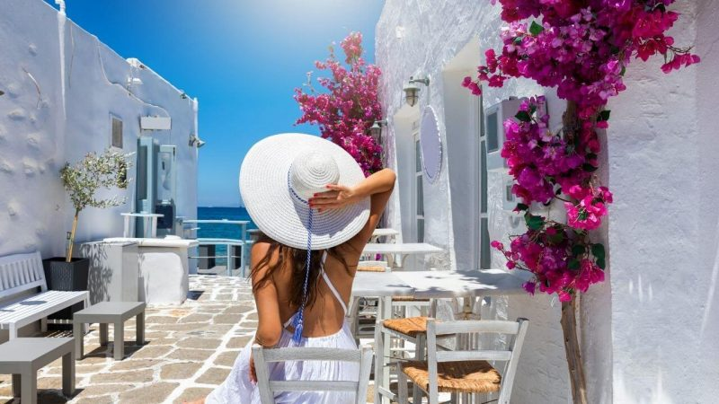 a girl holding her hat while walking along a white washed street in Greece