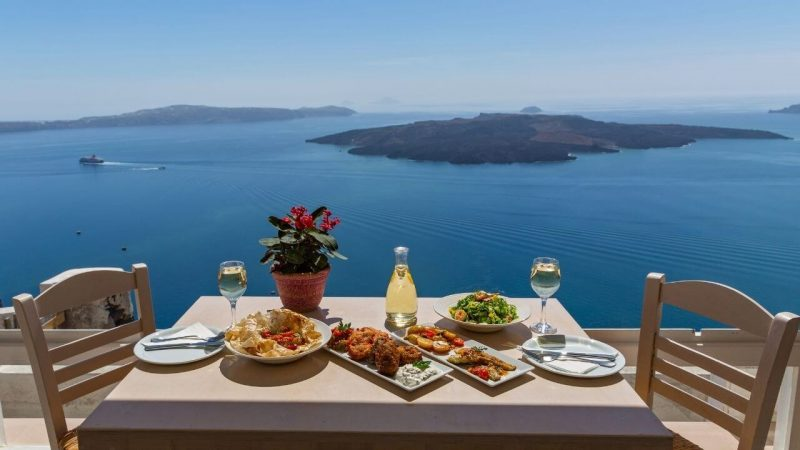 a table laid with food and wine looking out to sea